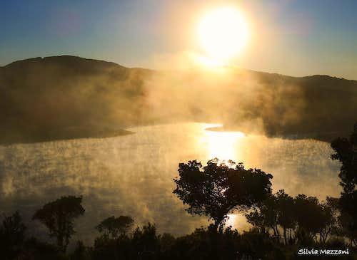 Mist dissolving at sunrise on Lago Alto di Flumendosa, Sardinia