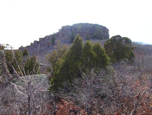 Castle Rock rugged summit pinnacles loom over it's lower slopes as seen from the parking lot