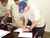 ChuckB signing the MAE with GaryR and JoeM looking on