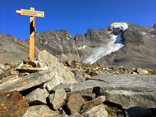 Wooden signpost amidst the high alpine rocks