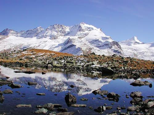 Gran Paradiso range reflected in a small lake between Pian Borgno and vallone delle Meyes