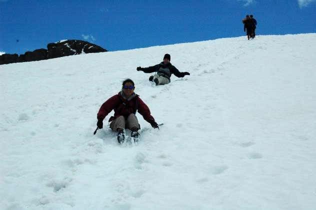 Shari and Lisa glissading down a snow field
