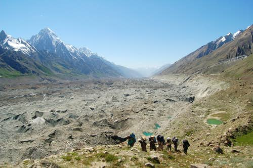 Porters trekking through the many meadows between the Pumari Chhish and Jutmo Glaciers with Makrong Chhish rising in the background