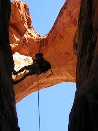 Rappel near arch in southern Utah