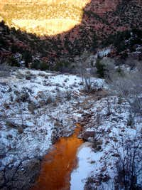 Alpenglow reflecting in half-frozen Pine Creek