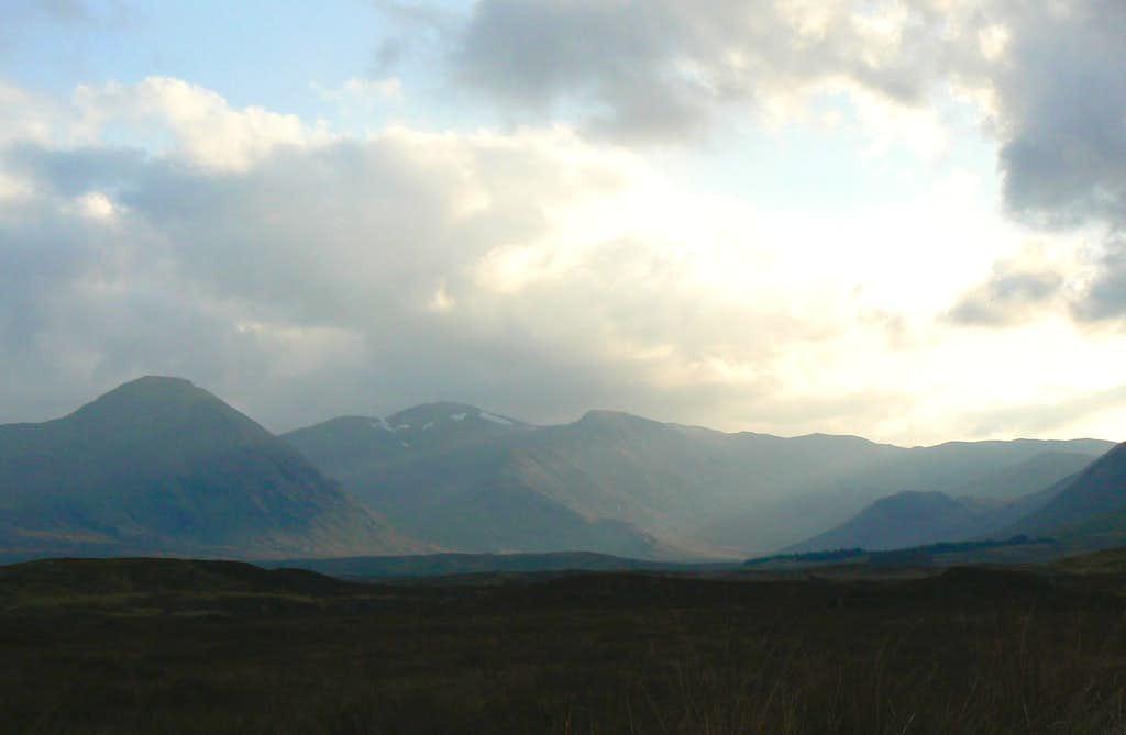 The sun breaks through over the Black Mount.
