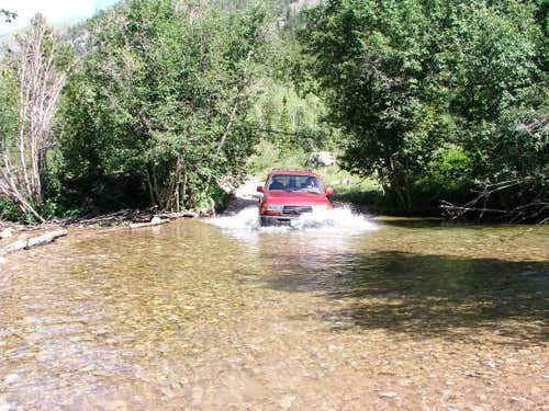 The Land Cruiser plunges into the first stream crossing