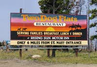 Billboard marking beginning of dirt road...