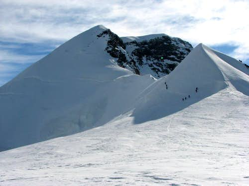 Climbers are climbing on the West Lyskamm from the pass Felik-joch.