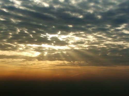 The sun shining through clouds