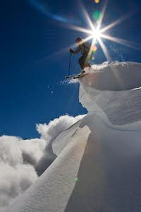 Skiing off a cornice on a perfect powder descent