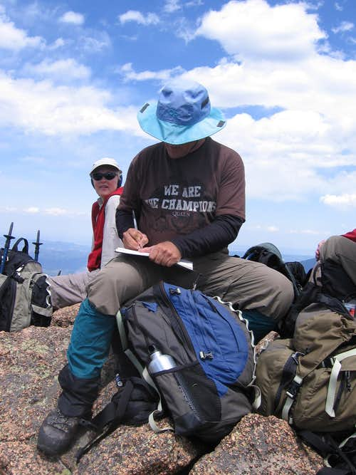 Aaron Johnson signs the register at the summit of Windy Peak....