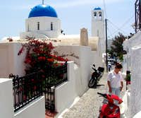 Santorini street scene showing the popular blue-domed cathedrals