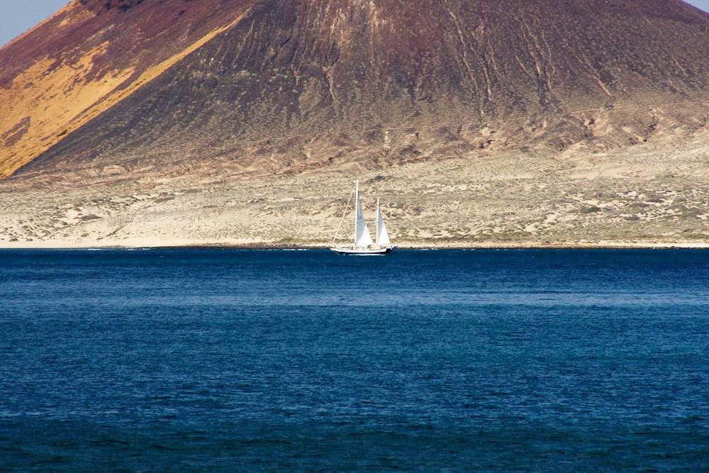 Sailing boat in front of Montaña Amarilla