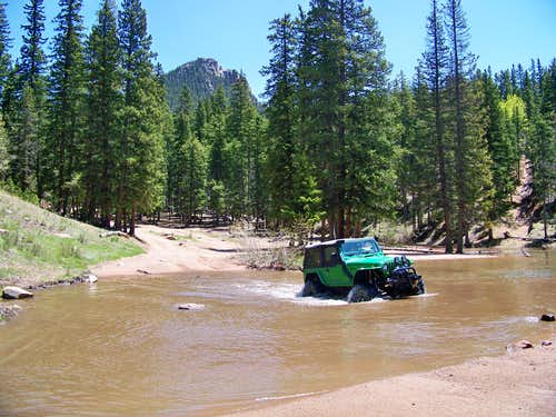 Jeep crossing a seasonal pond with Mount Big Chief in the background