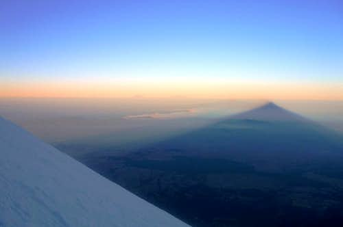 Shadow of Pico de Orizaba at sunrise, with a glance of Popocatépetl and Iztaccíhuatl at the horizon