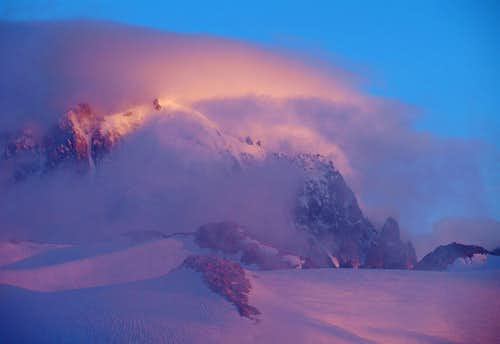 A glowing Aiguille Verte being hugged by cloud