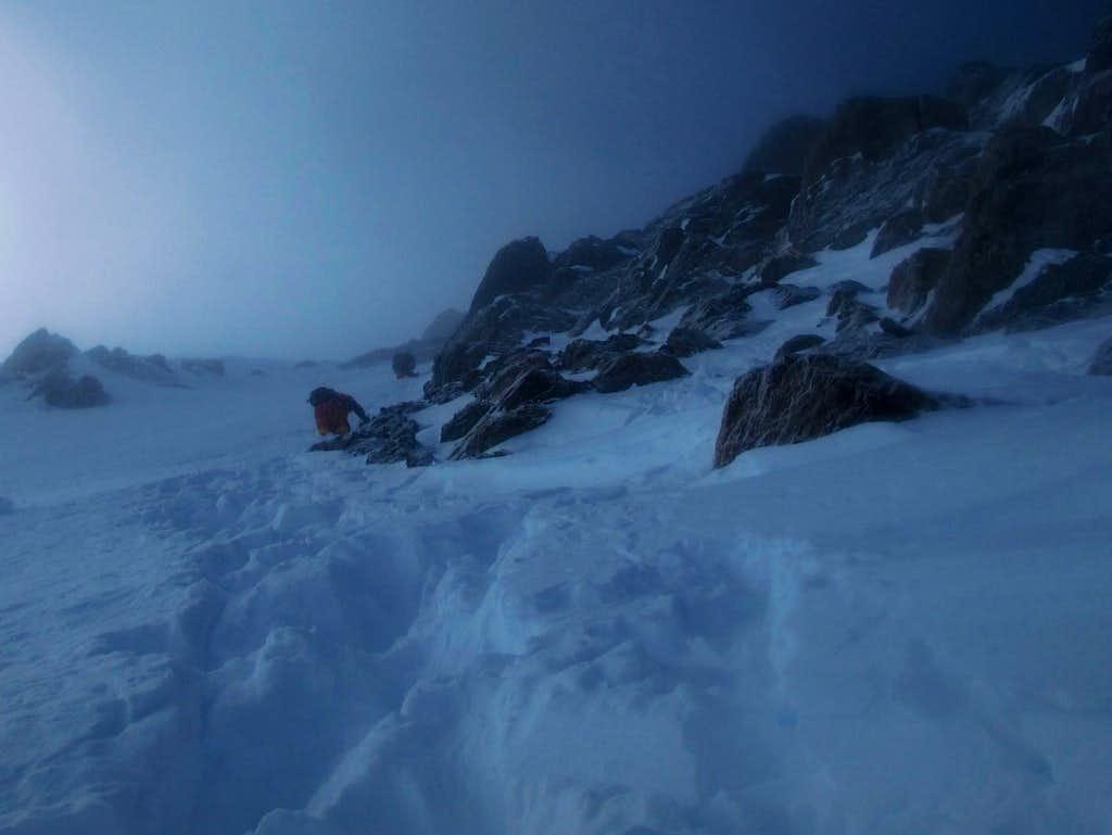 Czechs descending steep snow below summit ridge.
