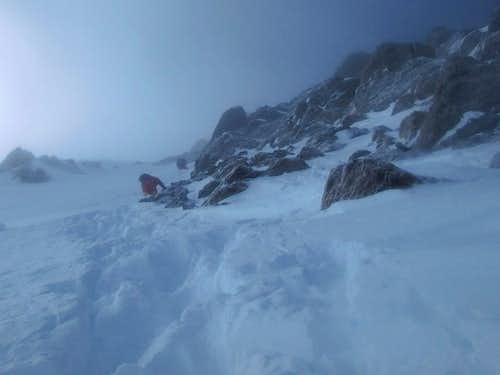 Czechs descending steep snow below summit ridge.