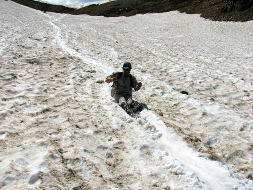 Dad sliding down snowfield