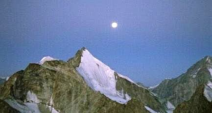 The first ray of sunshine and the moon above Obergabelhorn
