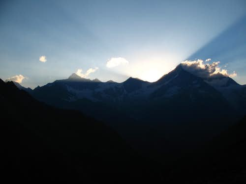 the sun is going down behind Rothorn and Weisshorn