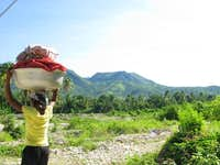 woman with heavy load in mountains on way to Pic La Selle