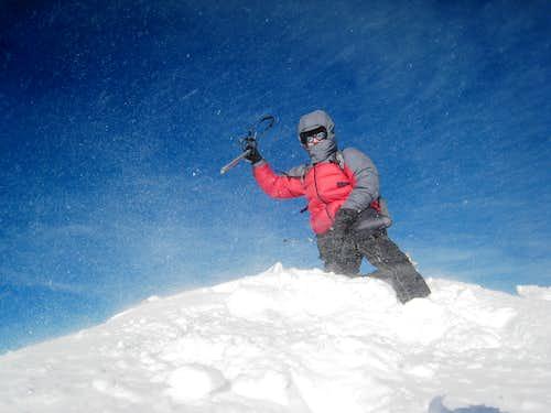 Overly-dramatic winter summit shot in stiff winds