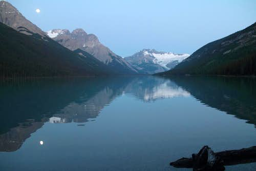 Glacier lake at dawn, with the moon still in the sky