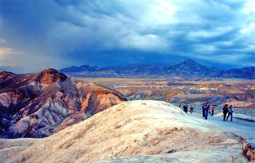Tourists approach Zabriski Point under swirling skies