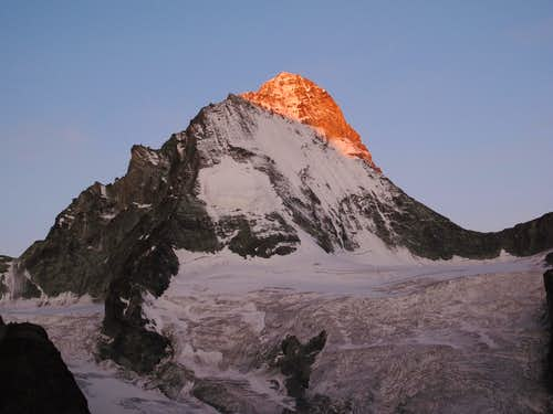 The first rays of sunlight hit the top of Dent Blanche