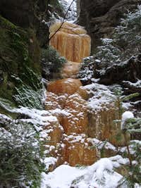 Orange colored frozen waterfall above the Polenztal valley