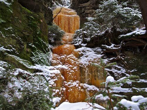 Orange colored frozen waterfall