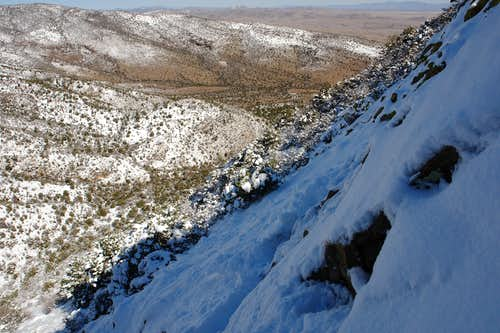 Traversing snow-covered slabs on the left side of the gully