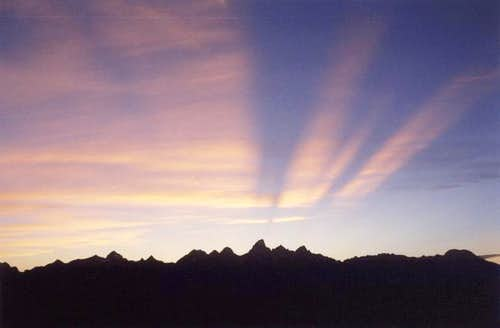 The sun sets behind the Teton...