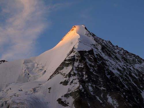 The very first rays of morning glow on the top of Obergabelhorn