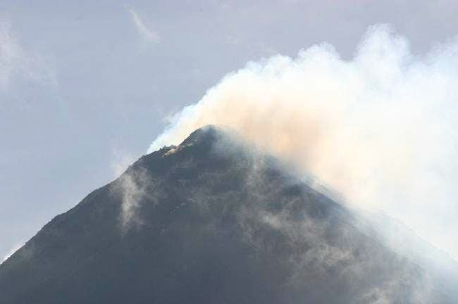 Arenal volcano puffing out smoke on a clear day