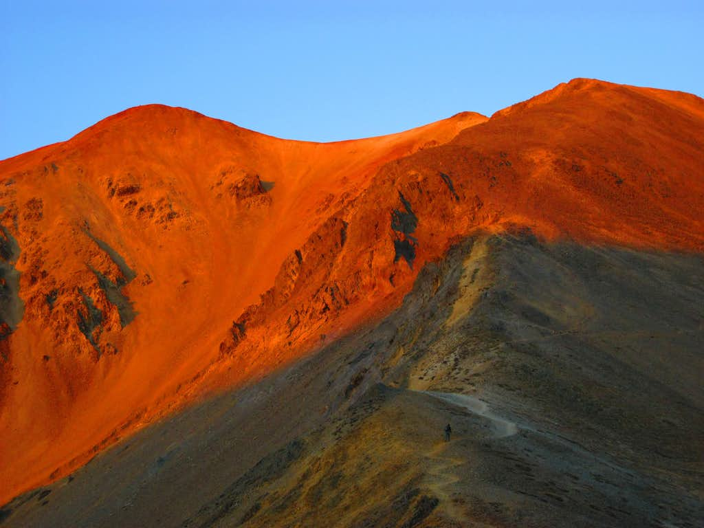 Morning Alpenglow burns on Redcloud Peak as a lone hiker heads up