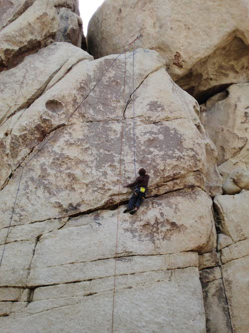 Closeup of a climber on a 5.11 route on Chimney Rock, Hidden Valley Campground, Joshua Tree National Park