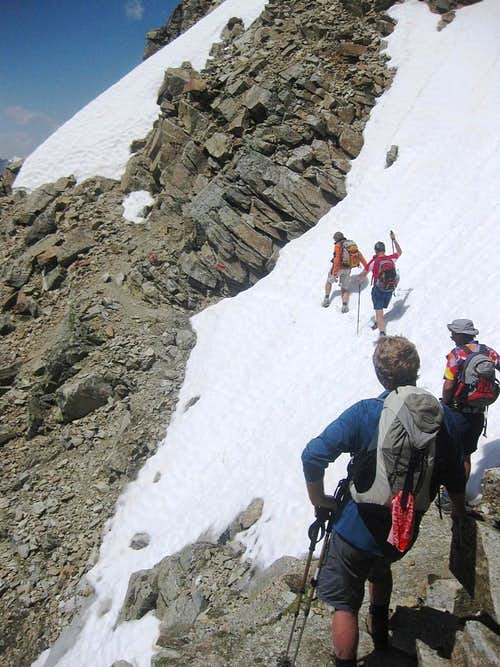 Carefully crossing a steep snowfield on the Hohe Geige normal route