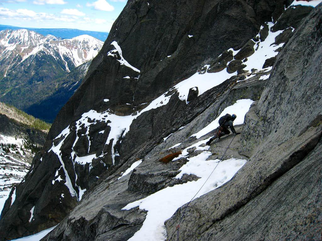 Danial leads across a wet, snowy ledge