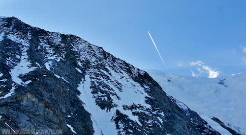 Plane crosses the sky over Aiguille du Gouter and Aiguille de Bionnassay