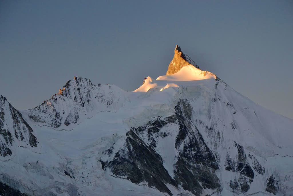 The first sunlight hits the summit rocks of Zinalrothorn