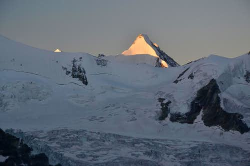 The first sunlight hits the ice north wall of Obergabelhorn