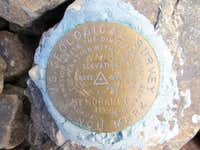 USGS summit marker on top of Mount Moran