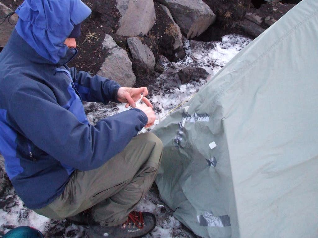 Repairing the tent after it got blown into a ravine.