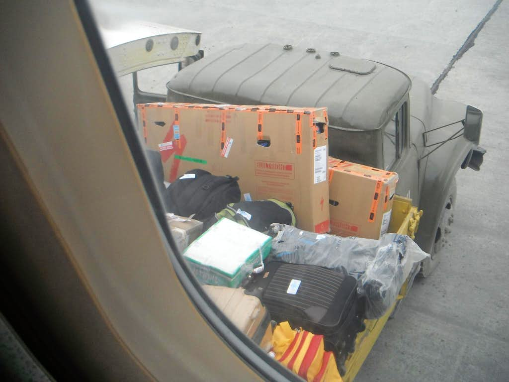 Loading our bicycle boxes and backpacks (clear bag) into the airplane.