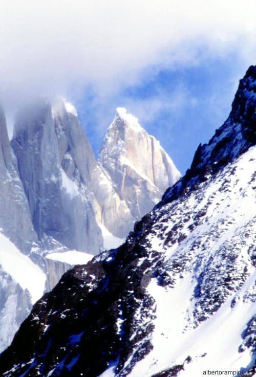 The snowy flat summit of El Mocho dominated by the gigantic Cerro Torre