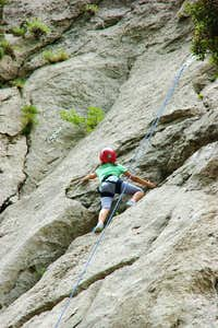 Child climber on a mountain wall