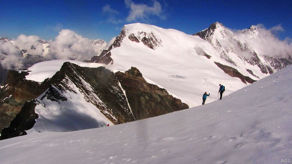 Climbers high on Allalinhorn, with Alphubel in the background